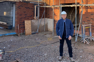 Ian Smethurst of Pearson Quality Homes wearing a hardhat and standing in front of a house under construction