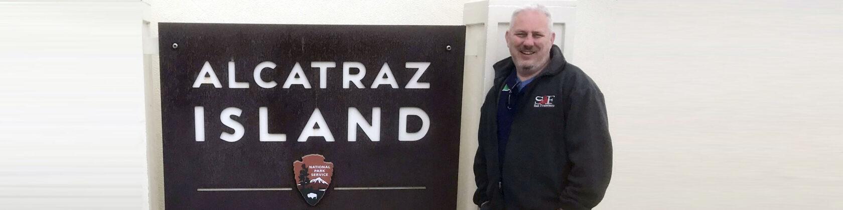 Mike Powell next to an Alcatraz Island sign
