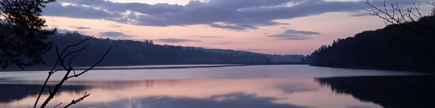 Reflection of the sky at dusk against a body of water, purple and pink hues