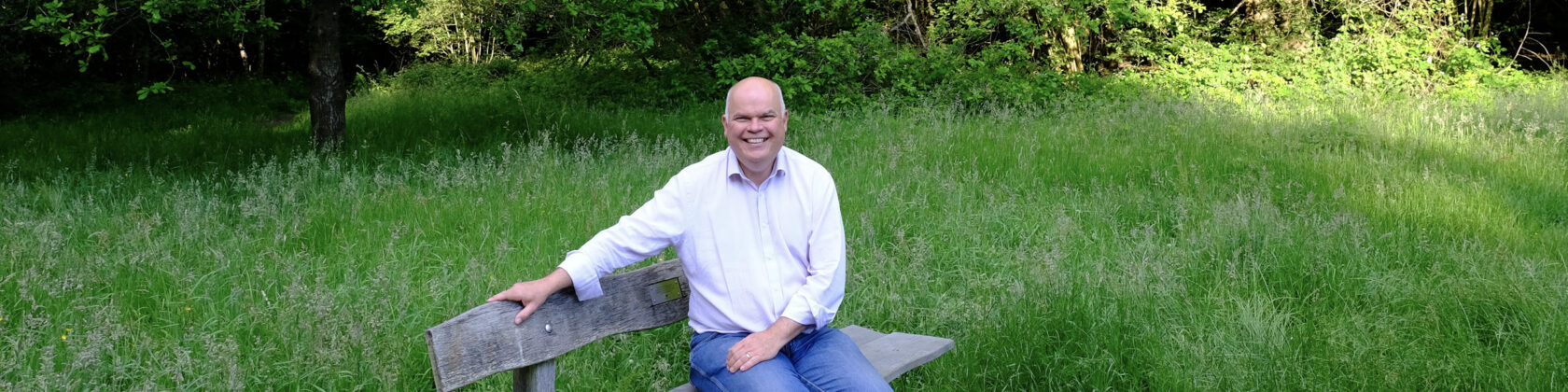 Portrait of Warren Ralls sitting on a bench surrounded by lush green grass