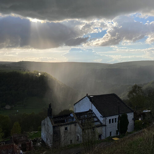 Panoramic view of an old cottage under cloudy sky