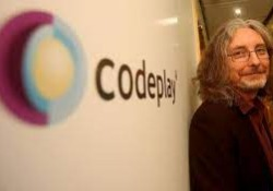 Codeplay employee stood against white wall with Codeplay logo on