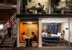 A split level office with various meeting rooms and people working